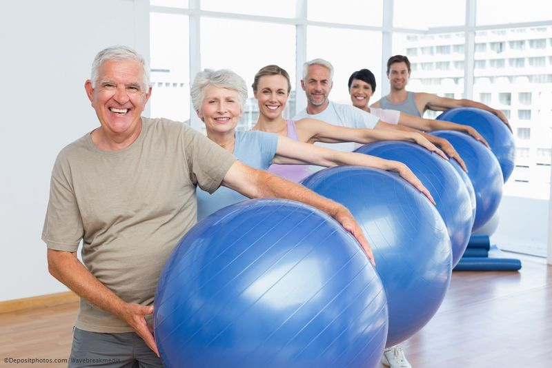 Mature people carrying exercise balls